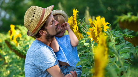Happy father and daughter are hugging in the field of sunflowers