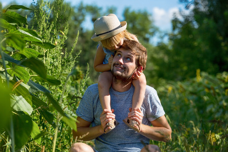 Happy little girl sitting on her fathers shoulders.