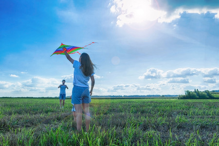 Happy parents and child are flying a kite in the field.