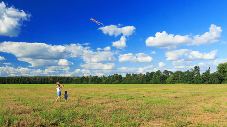 Mother and daughter flying a kite in a field Stockfoto
