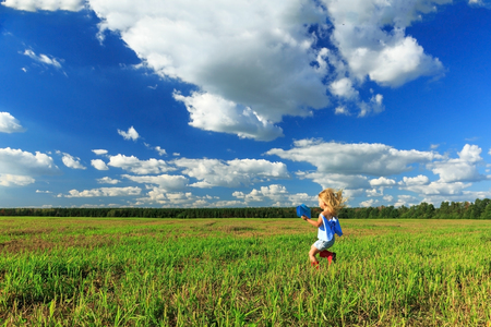 Little girl holding a paper plane in a hand and running in a field. The concept of the future. Stockfoto