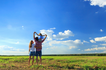Happy family. Mom dad and daughter look at the sun in the wheat field. Back view.