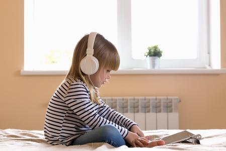 Focused girl with white headphones watching movie on laptop Stockfoto