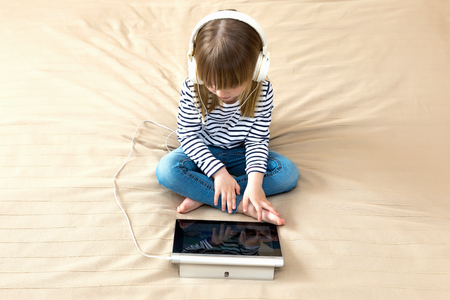 Top wiev portrait of little girl using laptop sitting on the bed.