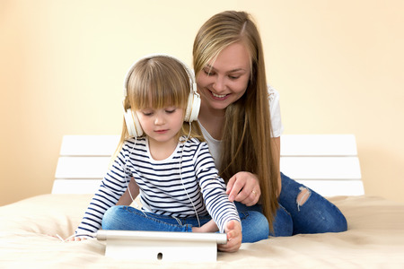 Mother and daughter using tablet together on the bed.
