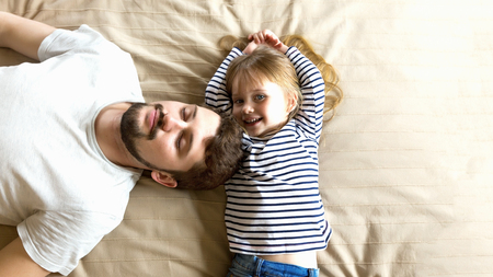 Handsome young father and happy daughter have fun together. Stockfoto