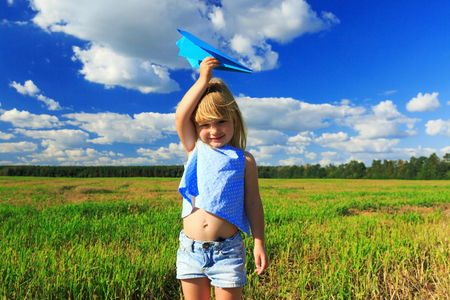 happy little girl holding a paper airplane in hand. The concept of the future.