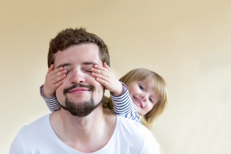 Happy family! The little girl covers her fathers eyes - she makes a surprise. Stockfoto