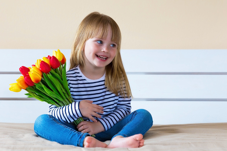 Little girl with colorful tulip flowers, laughing and looking to the side. Copy space, day light Stockfoto