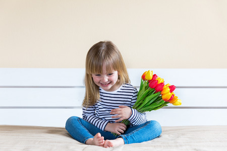 Happy Mothers day! Little girl holding tulip flowers, sits, smile and looking to camera. Copy space. Stockfoto