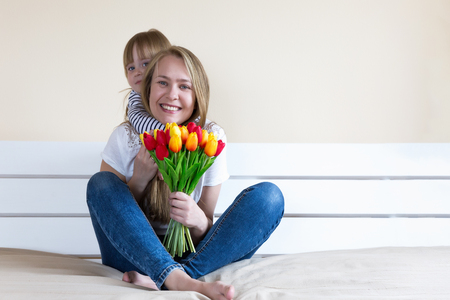 Happy mothers day! Little daughter congratulates mother and gives her colorful  tulip  flowers.