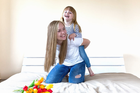 Happy mothers day! Mother and little daughter have fun in parents bed.