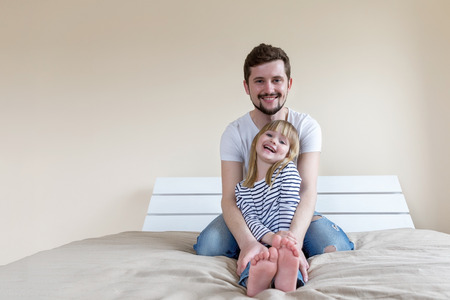 Father and daughter are sitting on the bed in the bedroom and laughing. Love and parental care.