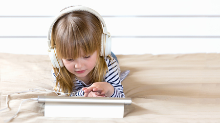 Focused little child using laptop with headphones studying  e-learning.