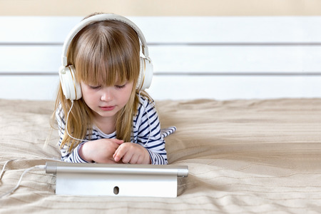 Happy cute girl watching videos streaming online on her laptop with headset at home Stockfoto