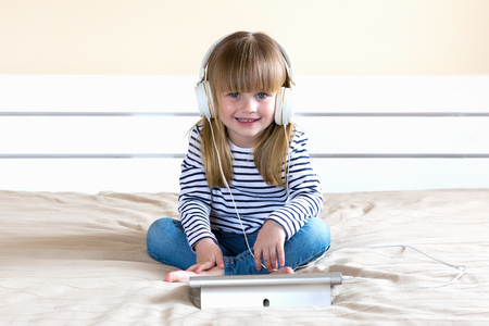 Cheerful little child using laptop with headphones studying online e-learning.
