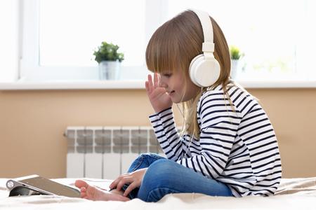 Modern childhood. Little baby girl using tablet inside home.