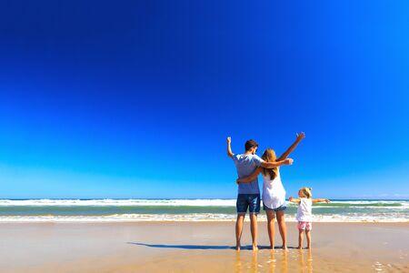Feliz padre madre y pequeño pararse en la orilla del mar en un día soleado. Copiar espacio, vista posterior.