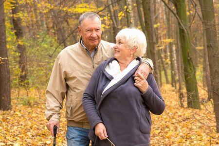 Happy elderly couple walking in an autumn park 版權商用圖片