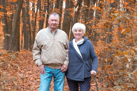 Happy two senior people walking in an autumn park