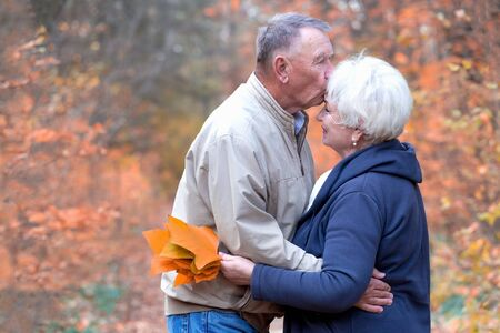 Elderly man kisses woman forehead in an autumn park 版權商用圖片
