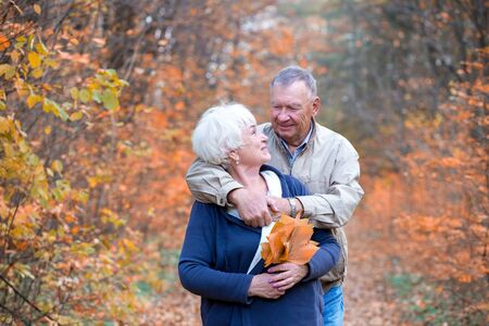 Happy senior couple hugs and talk in an autumn walk Archivio Fotografico