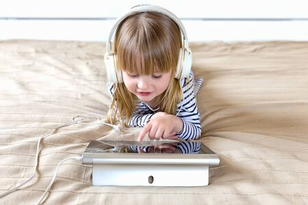 Cute little girl in casual clothes and headphones using a tablet and listening to music in the room.