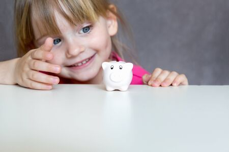 Cute blonde girl with piggy bank, copy space, interior