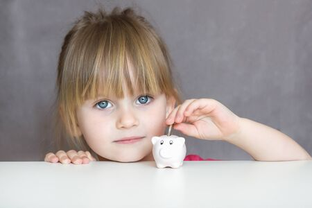 Education savings. Child holding piggy bank and putting coin. Looking in camera