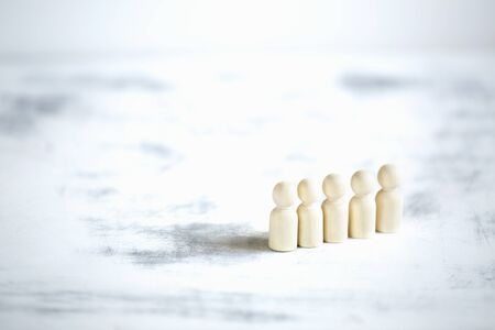 Wooden men stand in a row. Society concept.