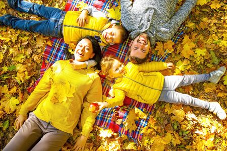 Happy family of forth in autumn park Stock Photo - 136867502