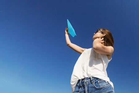 Young teenager girl is throwing a paper plane. Portrait in profile, copy space.