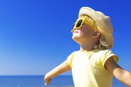 Happy little girl enjoying to the sun at the beach. Summer vacation concept