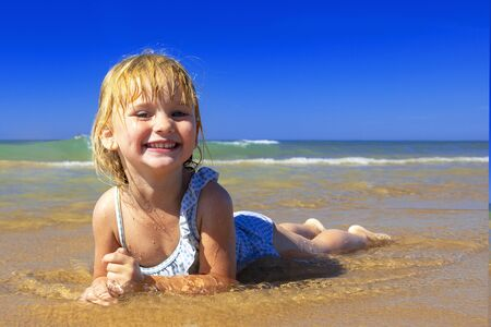 Happy little girl  lies on the beach and smiles