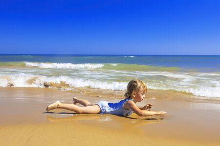 Happy little girl have fun at the seashore. Happy summer vacation.