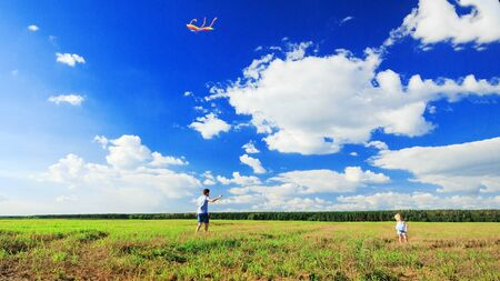 happy family Father and daughter flying a colorful kite in a field