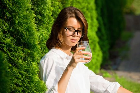 Close up portrait of girl drinks water.