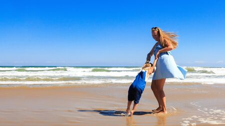 Mother and daughter are spinning and having fun on the beach at sunny day.