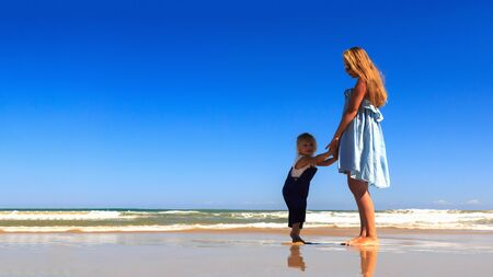 Happy Family! Mother and daughter stand on the beach. Copy space. Archivio Fotografico