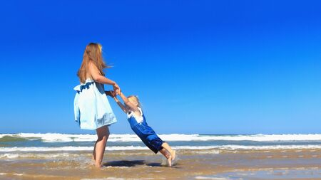 Mother and daughter spinning on the beach.