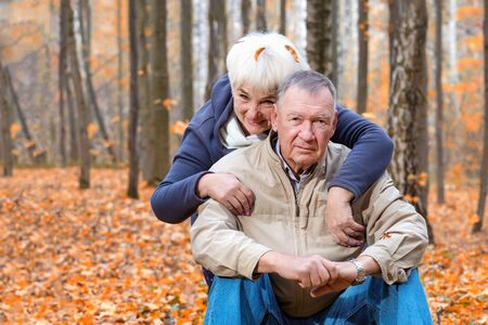 Happy senior couple sitting and smiling in an autumn park Archivio Fotografico
