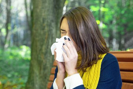 Woman blowing nose in an autumn park. Seasonal cold.