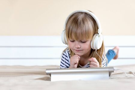 Happy cute girl watching videos streaming online on her laptop with headset at home Archivio Fotografico