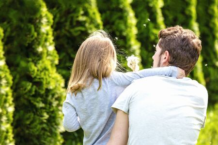 Back view. Father and daughter blowing dandelion flowers in sunny garden.