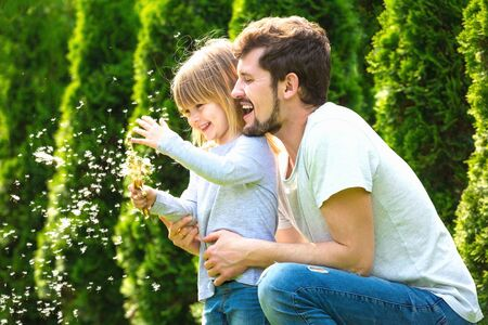 Happy father and daughter laugh and play with dandelion flowers Archivio Fotografico