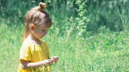 Happy little girl play in summer field in yellow dress. copy space Archivio Fotografico