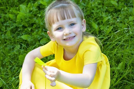 Happy little girl play in summer field in yellow dress