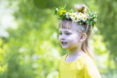Little girl in yellow handmade dress have fun on the meadow.