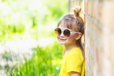Cute and happy little girl in yellow hand made dress outdoors portrait