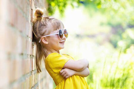 Happy little girl in yellow handmade dress. Close up summer portrait. Archivio Fotografico